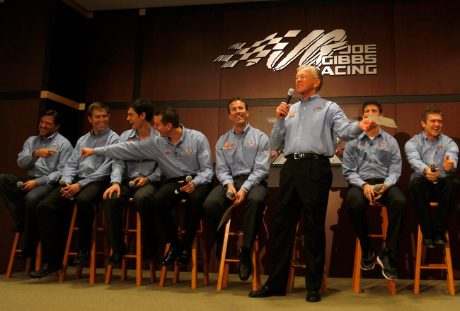 HUNTERSVILLE, NC - JANUARY 27:  Team owner Joe Gibbs (C) speaks, as (L-R) driver Tony Stewart, driver Brian Scott, driver Joey Logano, driver Kyle Busch, JGR President J.D. Gibbs, driver Denny Hamlin, driver Bobby Labonte, JGR senior vice president of rac