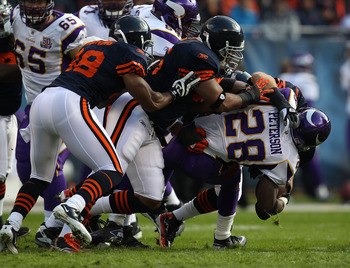 CHICAGO - NOVEMBER 14: (L-R) Rod Wilson #58, Lance Briggs #55 and Brian Urlacher #54 of the Chicago Bears tackle Adrian Peterson #28 of the Minnesota Vikings at Soldier Field on November 14, 2010 in Chicago, Illinois. The Bears defeated the Packers 27-13.
