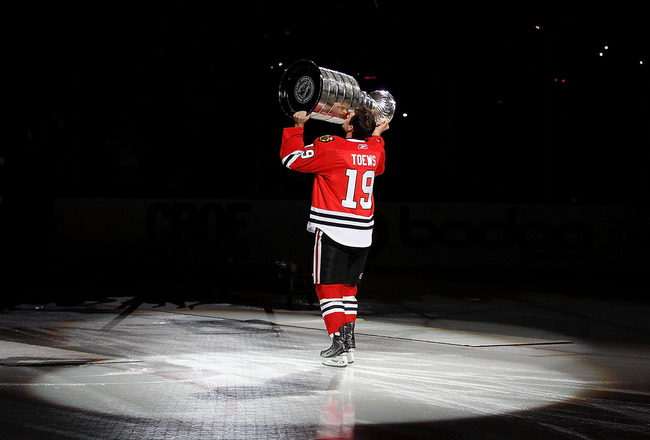 CHICAGO - OCTOBER 09: Jonathan Toews #19 of the Chicago Blackhawks kisses the Stanley Cup trophy as he skates across the ice in a ceremony before the Blackhawks season home opening game against the Detroit Red Wings at the United Center on October 9, 2010
