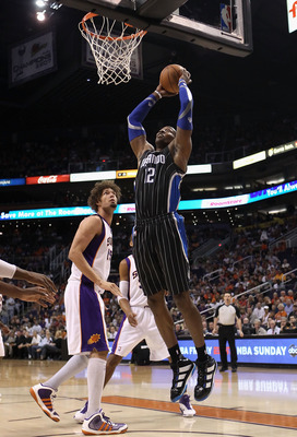 PHOENIX, AZ - MARCH 13:  Dwight Howard #12 of the Orlando Magic slam dunks the ball over Robin Lopez #15 of the Phoenix Suns during the NBA game at US Airways Center on March 13, 2011 in Phoenix, Arizona.  NOTE TO USER: User expressly acknowledges and agr
