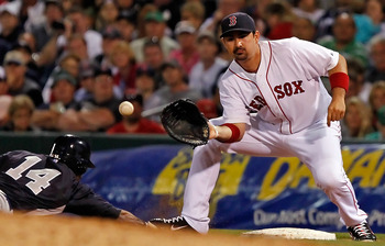 FORT MYERS, FL - MARCH 14:  First baseman Adrian Gonzalez #28 of the Boston Red Sox takes the throw at first as outfielder Curtis Granderson #14 of the New York Yankees gets back safely during a Grapefruit League Spring Training Game at City of Palms Park