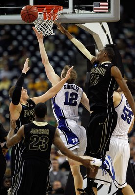 HOUSTON - MARCH 26: Kyle Singler #12 of the Duke Blue Devils puts up a shot against Lewis Jackson #23, D.J. Byrd #21 and JaJuan Johnson #25 of the Purdue Boilermakers during the south regional semifinal of the 2010 NCAA men's basketball tournament at Reli