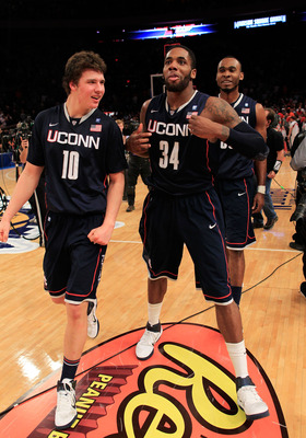 NEW YORK, NY - MARCH 11: Tyler Olander #10, Alex Oriakhi #34 and Charles Okwandu #35 of the Connecticut Huskies celebrate after defeating the Syracuse Orange during the semifinals of the 2011 Big East Men's Basketball Tournament presented by American Eagl