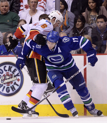 VANCOUVER, CANADA - FEBRUARY 12: Ryan Kesler #17 of the Vancouver Canucks tries to break free from Cory Sarich #6 of the Calgary Flames while battling for the loose puck during the third period in NHL action on February 12, 2011 at Rogers Arena in Vancouv
