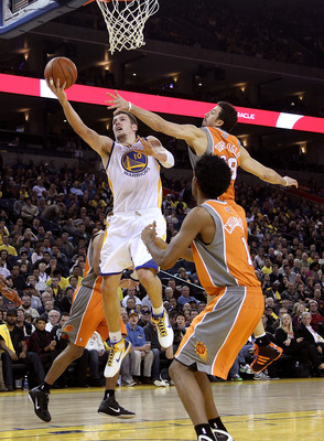 OAKLAND, CA - DECEMBER 02:  David Lee #10 of the Golden State Warriors drives to the basket against the Phoenix Suns at Oracle Arena on December 2, 2010 in Oakland, California. NOTE TO USER: User expressly acknowledges and agrees that, by downloading and