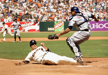 SAN FRANCISCO - JULY 18:  Travis Ishikawa #10 of the San Francisco Giants slides in to home plate under the tag of New York Mets catcher Henry Blanco #4 in the ninth inning AT&T Park on July 18, 2010 in San Francisco, California. Ishikawa was called out o