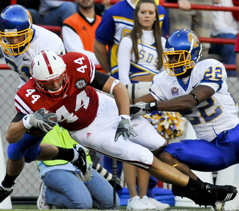 LINCOLN, NEBRASKA - SEPTEMBER 25: Nebraska Cornhuskers tight end Mike McNeill #44 gets knocked down by South Dakota State Jackrabbits cornerback Anthony Wise #22 and cornerback Cole Brodie #21 during first half action of their game at Memorial Stadium on