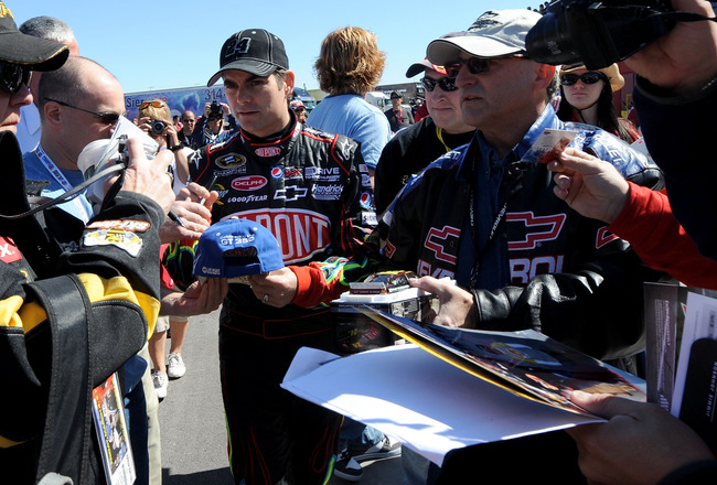 LAS VEGAS, NV - MARCH 04:  Jeff Gordon (C), driver of the #24 DuPont Chevrolet, signs autographs in the garage area during practice for the NASCAR Sprint Cup Series Kobalt Tools 400 at Las Vegas Motor Speedway on March 4, 2011 in Las Vegas, Nevada.  (Phot