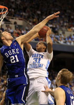 GREENSBORO, NC - MARCH 13:  John Henson #31 of the North Carolina Tar Heels shoots against Miles Plumlee #21 of the Duke Blue Devils during the second half in the championship game of the 2011 ACC men's basketball tournament at the Greensboro Coliseum on