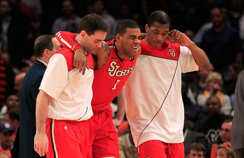 NEW YORK, NY - MARCH 10: D.J. Kennedy #1 of the St. John's Red Storm is helped off the court after being injured in the first half against the Syracuse Orange during the quarterfinals of the 2011 Big East Men's Basketball Tournament presented by American