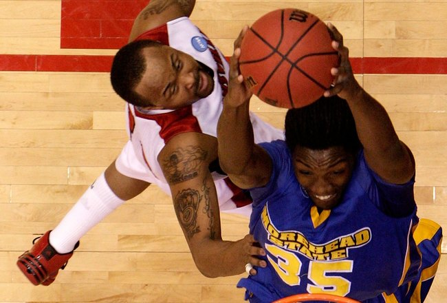DAYTON, OH - MARCH 20: Kenneth Faried #35 of the Morehead State Eagles drives to the hoop against Jerry Smith #34 of the Louisville Cardinals during the first round of the NCAA Division I Men's Basketball Tournament at the University of Dayton Arena on Ma