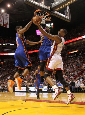 MIAMI, FL - FEBRUARY 27:  Chris Bosh #1 of the Miami Heat goes to the net against Amar'e Stoudemire #1 and Shawne Williams #3 of the New York Knicks during a game at American Airlines Arena on February 27, 2011 in Miami, Florida. NOTE TO USER: User expres