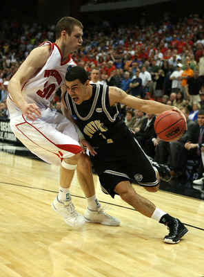JACKSONVILLE, FL - MARCH 19:  Cameron Rundles #1 of the Wofford Terriers tries to drive around Jon Leuer #30 of the Wisconsin Badgers in the first round of the 2010 NCAA men's basketball tournament at Jacksonville Veteran's Memorial Arena on March 19, 201