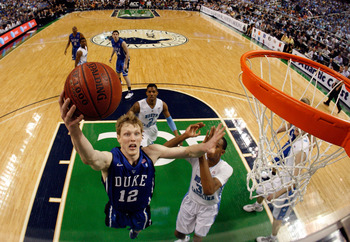 GREENSBORO, NC - MARCH 13:  Kyle Singler #12 of the Duke Blue Devils shoots against John Henson #31 of the North Carolina Tar Heels in the championship game of the 2011 ACC men's basketball tournament at the Greensboro Coliseum on March 13, 2011 in Greens