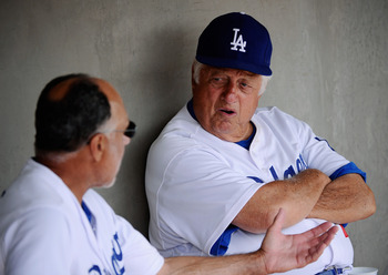 GLENDALE, AZ - MARCH 15:  Hall of Fame manager Tommy Lasorda #2 of the Los Angeles Dodgers speaks first base coach and Davey Lopes in the dugout prior to the start of the spring training baseball game against the Texas Rangers at Camelback Ranch on March