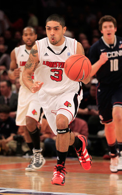 NEW YORK, NY - MARCH 12:  Peyton Siva #3 of the Louisville Cardinals brings the ball up court against the Connecticut Huskies during the championship of the 2011 Big East Men's Basketball Tournament presented by American Eagle Outfitters at Madison Square