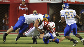 LINCOLN, NE - SEPTEMBER 25: Wide receiver Brandon Kinnie #84 of the Nebraska Cornhuskers gets tackled by by defensive tackle Andy Mink #52 cornerback Anthony Wise #22 of the South Dakota State Jackrabbits during first half action of their game at Memorial