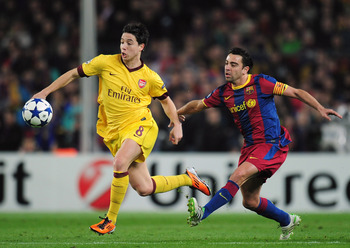 BARCELONA, SPAIN - MARCH 08:   Samir Nasri (L) of Arsenal is challenged by Xavi Hernandez of Barcelona during the UEFA Champions League round of 16 second leg match between Barcelona and Arsenal at the Nou Camp Stadium on March 8, 2011 in Barcelona, Spain