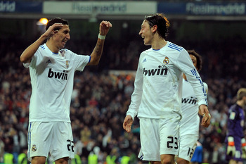 MADRID, SPAIN - JANUARY 13:  Mesut Ozil (R)of Real Madrid celebrates with Angel di Maria after scoring Real's third goal during the Copa del Rey quarter final first leg match between Real Madrid and Atletico Madrid at Estadio Santiago Bernabeu on January