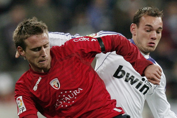 MADRID, SPAIN - DECEMBER 16:  Wesley Sneijder (R) of Real Madrid duels for the ball with Ignacio Monreal of Osasuna during the La Liga match between Real Madrid and Osasuna at the Santiago Bernabeu Stadium on December 16, 2007 in Madrid, Spain.  (Photo by