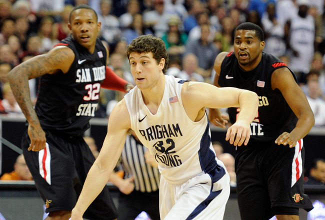 LAS VEGAS, NV - MARCH 12:  Jimmer Fredette #32 of the Brigham Young University Cougars drives in front of Billy White #32 and Chase Tapley #22 of the San Diego State Aztecs during the championship game of the Conoco Mountain West Conference Basketball tou