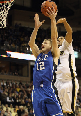 WINSTON SALEM, NC - JANUARY 22:  Kyle Singler #12 of the Duke Blue Devils drives to the basket against Ty Walker #40 of the Wake Forest Demon Deacons at Lawrence Joel Coliseum on January 22, 2011 in Winston Salem, North Carolina.  (Photo by Streeter Lecka