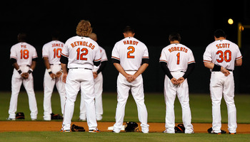 SARASOTA, FL - MARCH 07:  Infielders Mark Reynolds #12, J.J. Hardy #2, Brian Roberts #1 and Luke Scott #30 of the Baltimore Orioles bow their heads for the National Anthem just before the start of the Grapefruit League Spring Training Game against the New