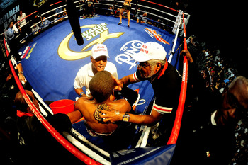 LOS ANGELES - AUGUST 27:  (EDITORS: A FISHEYE LENS WAS USED FOR THIS IMAGE) Carlos Fulgencio of Santo Domingo, DR gets help from his corner as he fights Abner Mares on August 27, 2009 in Los Angeles, California.  (Photo by Jacob de Golish/Getty Images)