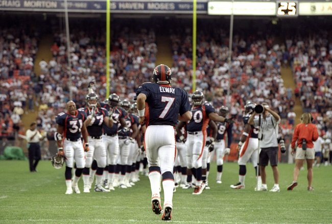 14 Aug 1998:  Quarterback John Elway #7 of the Denver Broncos runs on to the field prior to a pre-season game against the New Orleans Saints at the Mile High Stadium in Denver, Colorado. The Broncos defeated the Saints 17-10.