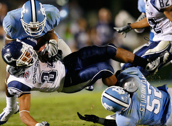 CHAPEL HILL, NC - OCTOBER 04:  Tailback Donald Brown #34 of the Connecticut Huskies is tackled by Kendric Burney #16 and Quan Sturdivant #52 of the North Carolina Tar Heels during the game at Kenan Stadium on October 4, 2008 in Chapel Hill, North Carolina