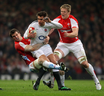 CARDIFF, WALES - FEBRUARY 04:  Toby Flood of England is tackled by Sam Warburton (L) and Bradley Davies (R) of Wales during the RBS 6 Nations Championship match between Wales and England at the Millennium Stadium on February 4, 2011 in Cardiff, Wales.  (P