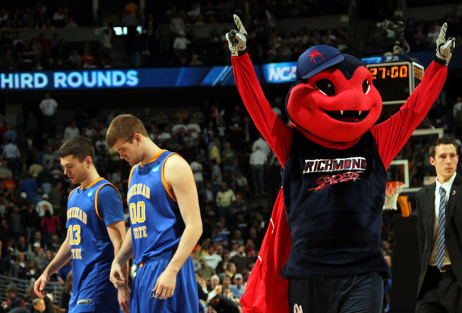 DENVER, CO - MARCH 19:  The Richmond Spiders mascot celebrates after the game as Ty Proffitt #13 and Drew Kelly #00 of the Morehead State Eagles walk off the court during the third round of the 2011 NCAA men's basketball tournament at Pepsi Center on Marc