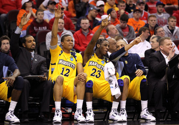 CLEVELAND, OH - MARCH 20: Erik Williams #12 and Dwight Buycks #23 of the Marquette Golden Eagles put their hands up with teammates while on the bench against the Syracuse Orange during the third of the 2011 NCAA men's basketball tournament at Quicken Loan