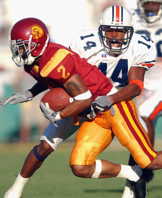 LOS ANGELES - SEPTEMBER 2:  Wide receiver Kareem Kelly #2 of the USC Trojans is tackled by defensiveback Carlos Rogers #14 of the Auburn Tigers at the Los Angeles Coliseum on September 2, 2002 in Los Angeles, California. USC defeated Auburn 24-17.  (Photo