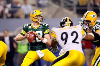ARLINGTON, TX - FEBRUARY 06:  Aaron Rodgers #12 of the Green Bay Packers looks to pass against James Harrison #92 of the Pittsburgh Steelers during Super Bowl XLV at Cowboys Stadium on February 6, 2011 in Arlington, Texas. The Packers won 31-25.  (Photo b