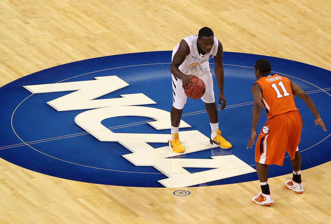 TAMPA, FL - MARCH 17:  Darryl Bryant #25 of the West Virginia Mountaineers brings the ball up court against Andre Young #11 of the Clemson Tigers during the second round of the 2011 NCAA men's basketball tournament at St. Pete Times Forum on March 17, 201