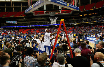 ATLANTA - MARCH 13:  Deandre Liggins #34 of the Kentucky Wildcats cuts down the net after their 70 to 54 win over the Florida Gators in the championship game of the SEC Men's Basketball Tournament at Georgia Dome on March 13, 2011 in Atlanta, Georgia.  (P