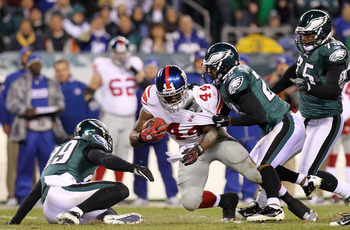 PHILADELPHIA, PA - NOVEMBER 21:  Ahmad Bradshaw #44 of the New York Giants is tackled by Dimitri Patterson #23 and Marlin Jackson #28 of the Philadelphia Eagles at Lincoln Financial Field on November 21, 2010 in Philadelphia, Pennsylvania.  (Photo by Nick