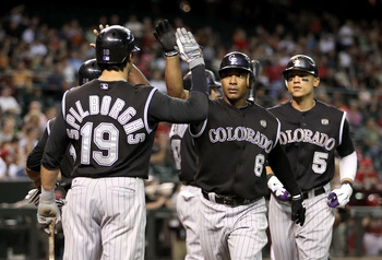 PHOENIX - SEPTEMBER 22:  Melvin Mora #6 of the Colorado Rockies celebrates with teammates Ryan Spilborghs #19, Jonathan Herrera #18 and Carlos Gonzalez #5 after Mora hit a three-run homerun against the Arizona Diamondbacks during the first inning of the M