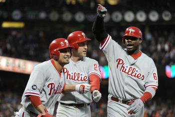 SAN FRANCISCO - OCTOBER 20:  (L-R) Shane Victorino #8, Chase Utley #26, and Ryan Howard #6 of the Philadelphia Phillies celebrate after Victorino and Utley scored on a double by Placido Polanco #27 against the San Francisco Giants in Game Four of the NLCS