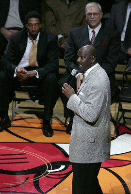 CHICAGO - DECEMBER 9:  Michael Jordan, formerly of the Chicago Bulls, speaks to the crowd as former teammate Scottie Pippen (L) and former coach Phil Jackson listen during a ceremony retiring Pippen's #33 at halftime of a game between the Bulls and the Lo