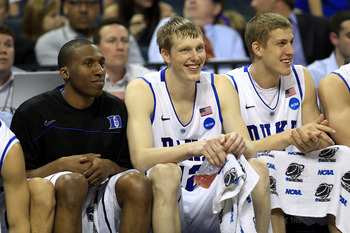 CHARLOTTE, NC - MARCH 18:  (L-R) Nolan Smith #2, Kyle Singler #12 and Mason Plumlee #5 of the Duke Blue Devils sit on the bench in the second half while taking on the Hampton Pirates during the second round of the 2011 NCAA men's basketball tournament at