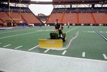 HONOLULU, HI - FEBRUARY 5:  Stadium grounds crew prepare the field as they remove rain water from the artificial turf prior to the 1995 NFL Pro Bowl at Aloha Stadium on February 5, 1995 in Honolulu, Hawaii.  The AFC defeated the NFC 41-13.  (Photo by Geor