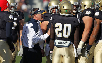 SOUTH BEND, IN - OCTOBER 30: Head coach Brian Kelly of the Notre Dame Fighting Irish talks to his offensive team including Cierre Wood #20 during a time-out against the Tulsa Golden Hurricane at Notre Dame Stadium on October 30, 2010 in South Bend, Indian