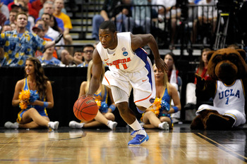 TAMPA, FL - MARCH 19:  Erving Walker #11 of the Florida Gators pushes the ball up court against the UCLA Bruins during the third round of the 2011 NCAA men's basketball tournament at St. Pete Times Forum on March 19, 2011 in Tampa, Florida. Florida won 73