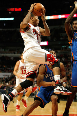 CHICAGO - JANUARY 04: Derrick Rose #1 of the Chicago Bulls leaps to pass against Russell Westbrook #0 and Serge Ibaka #9 of the Oklahoma City Thunder at the United Center on January 4, 2010 in Chicago, Illinois. The Thunder defeated the Bulls 98-85. NOTE