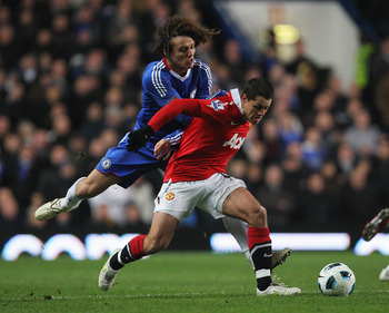 Luiz forcing Manchester United's Hernandez backwards.