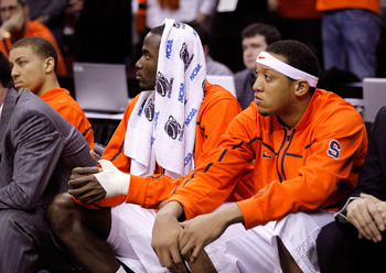 CLEVELAND, OH - MARCH 20: Baye Moussa Keita #12 and Mookie Jones #21 of the Syracuse Orange look on from the bench after being defeated by the Marquette Golden Eagles during the third of the 2011 NCAA men's basketball tournament at Quicken Loans Arena on