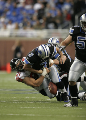 DETROIT - NOVEMBER 24:  Joey Harrington #3 of the Detroit Lions fumbles while being sacked by Patrick Kerney #97 of the Atlanta Falcons during a NFL game at Ford Field on November 24, 2005 in Detroit, Michigan.  The Falcons won the game, 27-7.  (Photo by