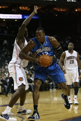 CHARLOTTE, NC - NOVEMBER 10:  Dwight Howard #12 of the Orlando Magic drives past Nazr Mohammed #13 of the Charlotte Bobcats during the game on November 10, 2009 at Time Warner Cable Arena in Charlotte, North Carolina.  The Magic won 93-81.  NOTE TO USER: